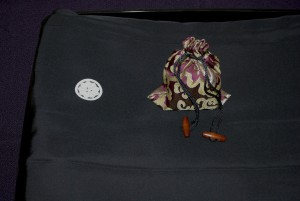 An image of a decorative bag containing a wooden stamp called an Inshou and a traditional folded Japanese outfit known as a Montsuki.